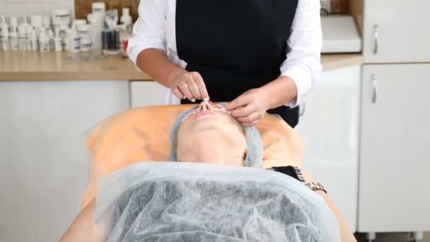 V klinice krásy. Záběr kosmetička a ženy starší klienta při injectional postupu. Mezoterapie Kosmetologické procedury. HD