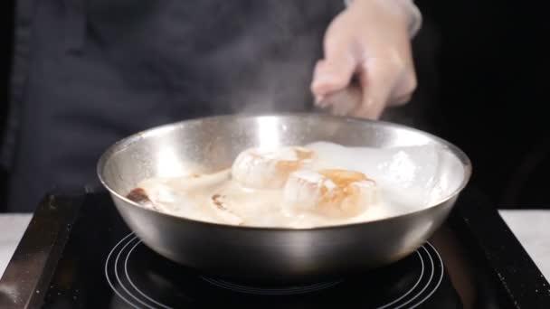 Kochen im Restaurant professionelle Herd in Handschuhen rühren Pfanne mit Jakobsmuscheln kochend in Sahnesauce. Zeitlupe. hd