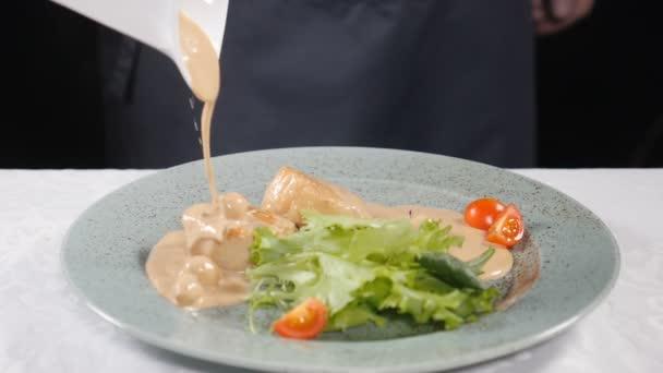 Kuchař, vaření. Příprava jídla. Sporák vylévající smetaně na misku s mušlemi a svěží mix salátu a rukoly, zpomalené. HD