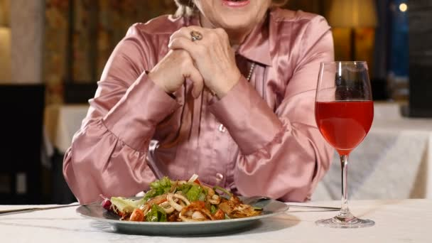 Unrecognizable retired woman sits in restaurant with vegetable salad and a glass of fresh fruit drink on table. Senior model in her 70s. 4k