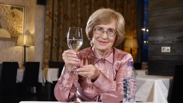 Senior waman looing at glass of still water poured in a glass. An old-aged person sits in a restaurant.