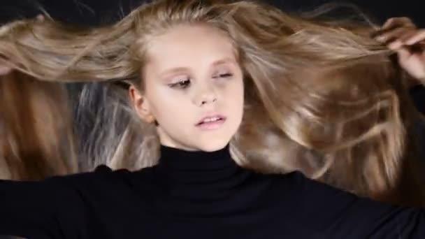 Porträt eines kleinen Modells im Atelier auf schwarzem Hintergrund. Ihr Haar berühren, in die Kamera schauen, posieren.
