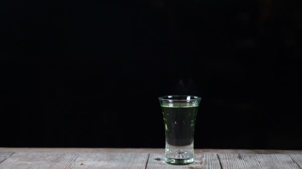 Schöne Zeitlupe Schuss von Barista cocktail in einer Bar machen. Flammen aufgehenden aus ein alkoholisches Getränk in ein Glas oder einen Schuss auf schwarzem Hintergrund isoliert brennen. HD