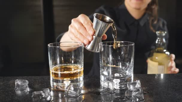 Ženské barman nalil whisky ze štamprle ve zpomaleném filmu. K nepoznání ženské barman v černých uniformách. HD