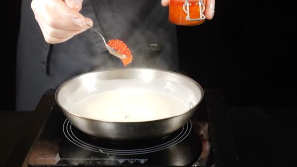 Jemné jídelní koncepce. Kuchař, červený kaviár nabytí smetaně šije v fruing pánvi. Restaurace konceptu kuchyně. Zpomalený pohyb. HD