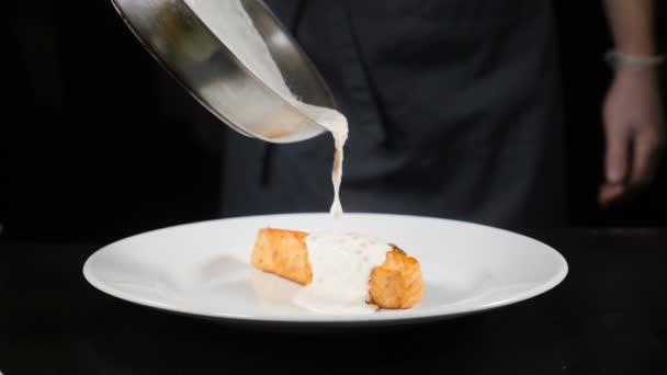 Výtečná kuchyně. Kuchaři v rukavicích, nalil jen podomácku smetaně na smažené filé pstruhu v pomalém pohybu. Restaurace jídlo koncept. HD