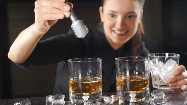 Ženské barman shození kostky ledu do sklenice s whisky v pomalém pohybu. Ice, padají šplouchání. Mladá žena barman připravuje alkoholické koktejly. HD
