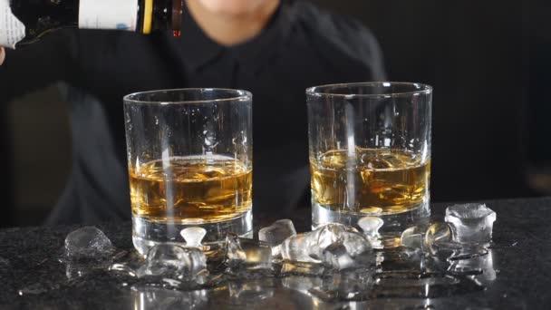 Cocktailherstellung. Barkeeper macht Cocktail mit Alkohol an der Theke und fügt ein paar Tropfen in Zeitlupe hinzu. Barfrau in schwarzer Uniform lächelt, während sie Getränke zubereitet. hd