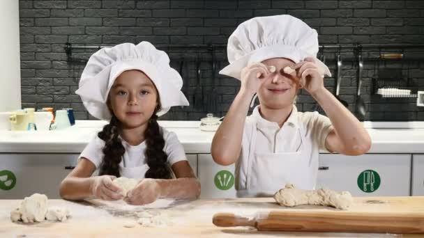 Děti baví vaření společně ve vlastní kuchyni. Děti šéfkuchař koncept. Těsto, mouku a váleček na stole. 4k