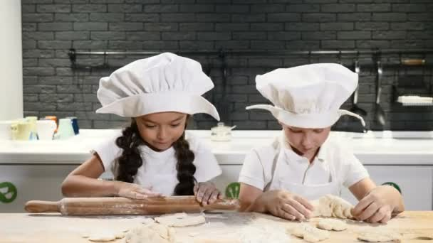 Cute kids in chef hats cook cookies and pies in private house. Kitchen utensil on the background. 4k