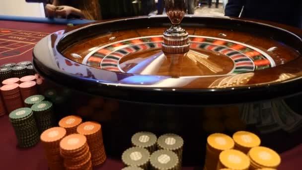 Casino téma. v ruletě v pohybu, bílé koule rotující. Smůly a štěstí koncepce. Kolo rulety běží. Městské centra noční zábavy. Krupiérův list přesune ruletě. HD