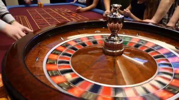Detailní záběr kasino ruleta točení kolem s kasinové žetony do hromady poblíž. Ruce urecognizable lidí s karty a čipy, lidé hazardu. Casino koncept. HD