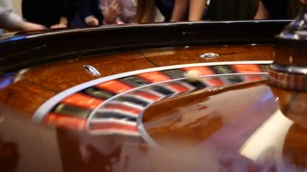 Closeup shot of casino roulette spinning around with casino chips put in piles near. Hands of urecognizable people holding cards and chips, people gambling. Casino concept. Dealer hand moves the