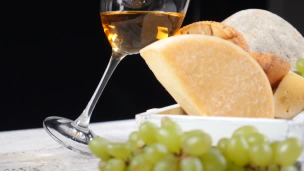 Wine and cheese concept. Food art concept. Cheese lovers. Variety of cheese placed on wooden board with black background. hd