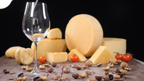 White wine is poured into a glass with a varieyty of hard cheese on background. Food art concept. Restaurant serving. Catering concept. Holidays festive concept. hd