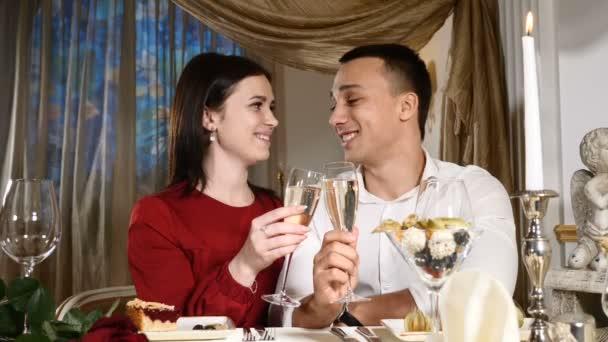 Mladý pár opékání šampaňské v restauraci. Na rande. Mladý muž a žena na romantickou večeři, pití v restauraci, slaví Valentýn. Romantická koncepce a nešťastná láska. HD