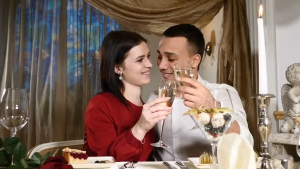 Young Couple Toasting champagne In Restaurant. Dating. Young man and woman on romantic dinner drinking at restaurant, celebrating valentine day.Romantic concept and love affairs. hd