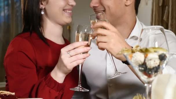Verliebte klirren bei einem Date in einem Restaurant mit Gläsern. Nahaufnahme. junger Mann und Frau beim romantischen Abendessen im Restaurant, das am 14. Februar gefeiert wird. romantisches Konzept und Liebesbeziehungen. hd