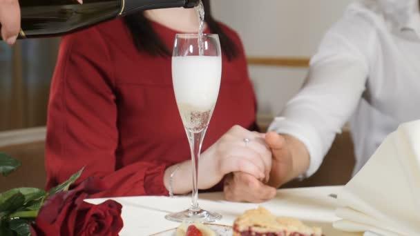Ehekonzept. Liebe und romantische Beziehungen. Kellner gießt Champagner in Glas für Paar in Zeitlupe. Nahaufnahme von Hand und einem Glas mit alkoholischen Getränken in Zeitlupe. hd