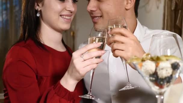 junges Paar prostet Champagner im Restaurant zu. Datierung. junge Mann und Frau beim romantischen Abendessen trinken im Restaurant, feiern Valentinstag. romantisches Konzept und Liebesbeziehungen. hd