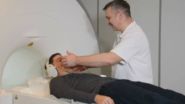 Computer tomography concept. Health concept. Person gets scanned by magnetic resonance imaging scanner in modern hospital.Male radiology specialist in white coat preparing patient for CT MRI procedure