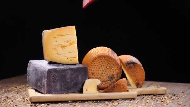Food video. Luxury food concept. Cheese restaurant serving. Food art concept. Variety of hard cheese put on wooden board. Pods of red pepper falling down in slow motion. hd