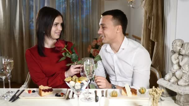 Couple with a rose hugging. Couple on date in restaurant. Man and woman love each other. Romantic composition. Romantic date of two attractive people, woman taking rose and kissing boyfriend. hd