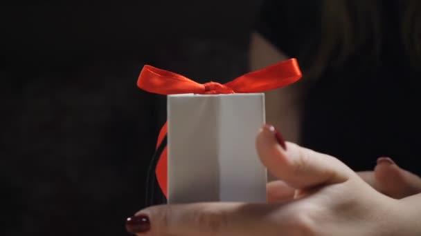 Temný obraz. Zblízka ženské prsty ukazuje kniha Dárková krabice s červenou stužkou a luk. otevření dárek dárkové krabici jako žena rozváže uzel luk na černém pozadí. HD