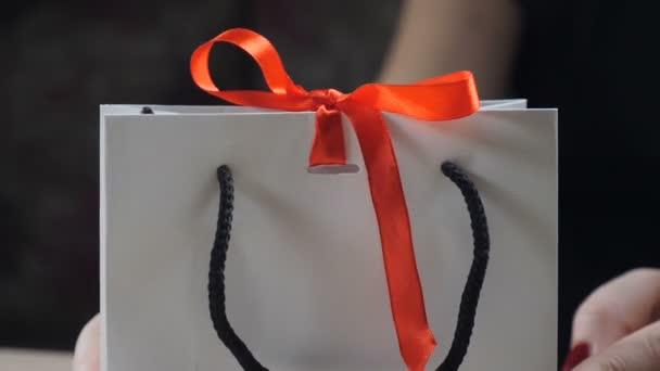Zblízka ženské prsty ukazuje kniha Dárková krabice s červenou stužkou a luk. otevření dárek dárkové krabici jako žena rozváže uzel luk na černém pozadí. HD