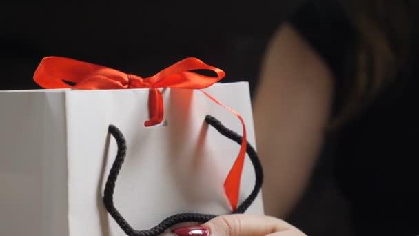 Obtékání přítomen. Ženské prsty vázaný červenou stuhou luk na krabičce. Detailní záběr žena rukou balení přítomné na stole. luk na vánoční dárek, dárek k narozeninám, současná koncepce nový rok.