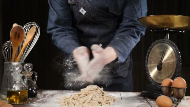 Šéfkuchař, tleskání rukou s moukou zároveň těsta pro pizzu, těstoviny, pečení chleba a pečivo sladkosti. Zpomalený pohyb. Profesionální cukrář kuchař tleská rukama a prášek mouchy. Nádobí, jen těstoviny