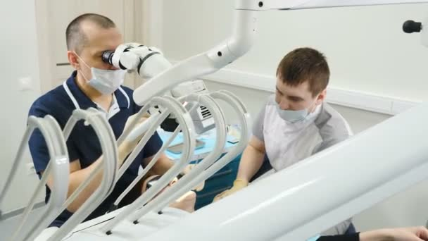 Doctor using microscope. Dentist treating patient in modern dental clinic. Orthodontist works with an assistant. The operation is carried out using special Dental Intraoral Check Digital Micro Camera