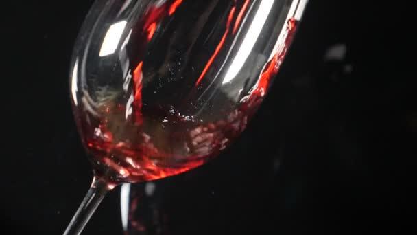 Sklo na černém pozadí. Červené víno se nalévá v pomalém pohybu. Vinařství. víno, šplouchání. HD