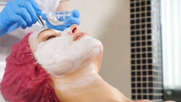 Attraktive weibliche Kundin mit Gesichtsmaske im Beauty-Salon. Die Gesichtsmaske mit einem Pinsel in der Dermatologie-Klinik auf das weibliche Gesicht auftragen. Spa-Therapie für junge Frau. Kosmetikerin mit Gesichtsmaske