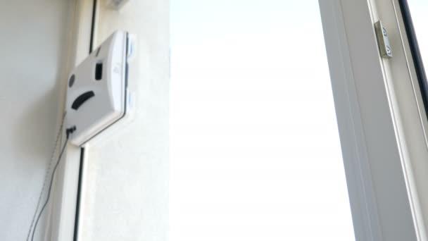 Čistý servis. Moderní způsob čištění oken. Robotická skleněná podložka pohybující se a otáčející se na okénku v soukromém bytě. Automatická skleněná podložka pracující na okénku bytu, uzavření. 4k