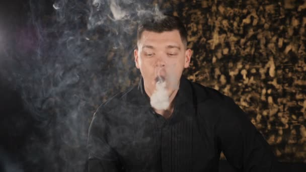Handsome young man smoking hookah. caucasian guy smoking flavored tobacco. Blow out smoke close-up on dark background. round form of vapor is flying in the air. Magic art fog, slow motion. hd