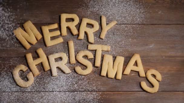 Koncept šťastný nový rok. Veselý vánoční lístek s koláčky na hnědém dřevěném pozadí. Bílý prášek upadajícího do pomalého pohybu. Hd