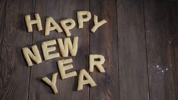Šťastný nový rok sušenky na hnědé dřevěné desce s prázdným prostorem pro poznámky. Pojem svátek a dovolená. Bílý cukr v pomalém pohybu. Hd