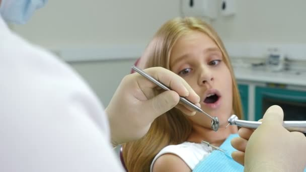 Little afraid girl at dentist office. Health and dental care. Closeup shot of dentist with drill and mirror in hands. 4K footage.