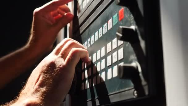 Detailní záběr mužských rukou mačkajících tlačítka na průmyslovém zařízení. Inženýr ovládající automatizovanou výrobní linku. Tovární specialista pracující s ovládacím panelem obráběcího stroje. 4k