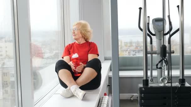 Docela aktivní důchodkyně v červeném tričku sedící na parapetu v tělocvičně. Starší osoba držící láhev s vodou. Klidná stará babička se dívá na okno ve fitness klubu. Shot in 4k