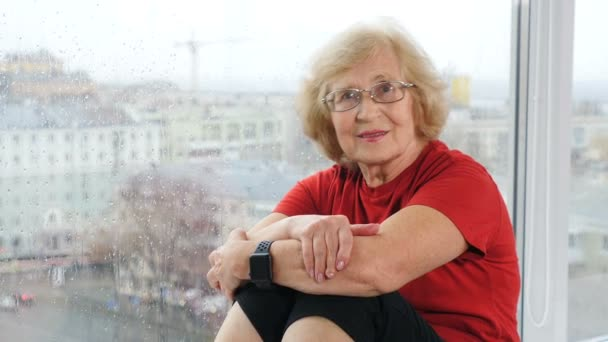 Porträt einer Rentnerin im T-Shirt, die in die Kamera blickt. Ein älterer, freundlich dreinblickender Rentner sitzt auf einem Fensterbrett mit Panoramafenstern dahinter. Schuss in 4k