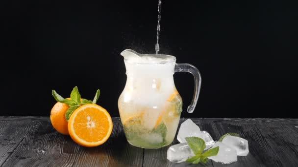 Szénsavas hideg víz öntése átlátszó üvegbe, felszeletelt narancssárga és jégkockákkal. Lassú mozgás. Fekete háttér. A csapos friss koktélt készít a nyáron. Koktélparti, éjszakai élet és nightclub. Teljes hd
