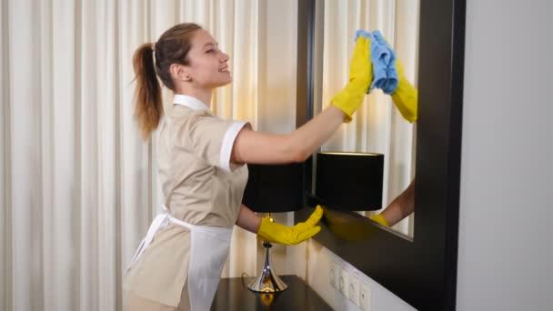 Moderner Reinigungsservice. Junge hübsche Frau vom Hotelpersonal wischt Spiegel im Wohnzimmer. Das Hausmädchen in Schutzhandschuhen putzt den Spiegel und lächelt dann in die Kamera. 4 k Filmmaterial