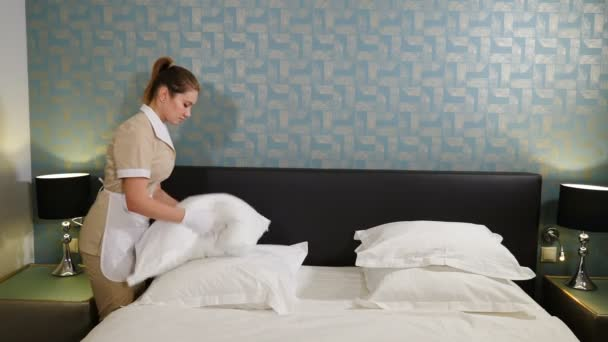 Professional cleaning service. Smiling chambermaid in unifrom making bed and beating and arranging pillows preparing room for visitors. Woman fluffing up pillows. 4 k video