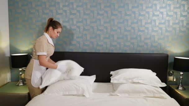 Profesionální úklid. Usmívající se pokojská v jednolůžkové posteli, mlátící a aranžující polštáře, připravující místnost pro návštěvníky. Žena nadýmající polštáře. 4 k video