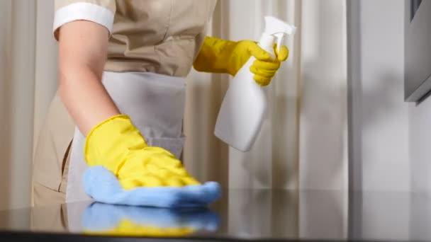 Reinigung im Hotel. Nahaufnahme einer jungen Haushälterin im Schürzenputzen, die mit Mikrofasertuch die Tischfläche wischt, blauer Lappen, die Putzfrau wischt vorsichtig die Oberfläche des Holztisches ab. 4 k Video