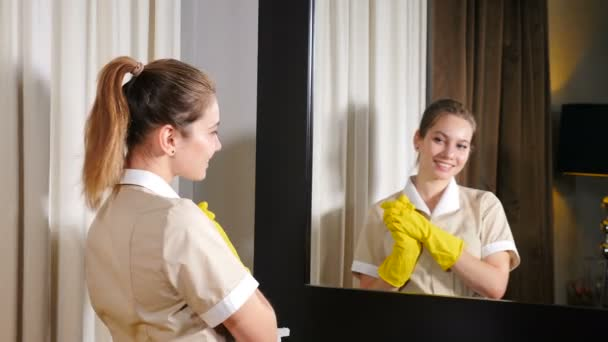 Moderner Reinigungsservice. Junge hübsche Frau vom Hotelpersonal wischt Spiegel im Wohnzimmer und lächelt ihr Spiegelbild an. Hausmädchen in Schutzhandschuhen Putzspiegel. 4 k Filmmaterial