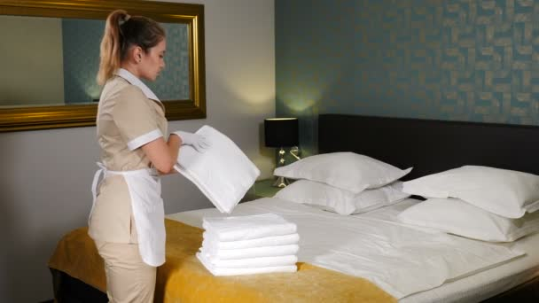Cleaning service. Close-up of maid hands putting one white towel on top of stack with fresh bath towels on the bed sheet. Room service maid. 4 k video