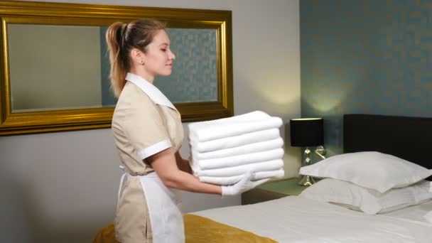 Professional cleaning service. Pretty maid holding stack of folded clean towels then throwing it up smiling at camera with king-sized bed in background. Room preparation for guests. 4 k video